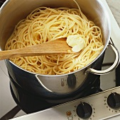 Putting butter on cooked pasta
