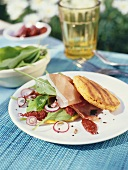 Grilled corn cakes with prosciutto and Mediterranean salad