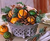 Schale mit gespickten Zitrusfrüchten, Gewürzen und Zweigen