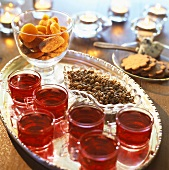 Warm cranberry punch and sweet nibbles on a tray