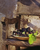 Figs in earthenware dish on wooden bench out of doors