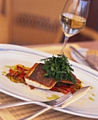 Sea bass on peppers with fresh herbs