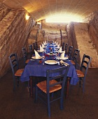 Table laid for special occasion in a vaulted cellar