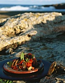 Cooked mussels with tomatoes and herbs on rocks by sea