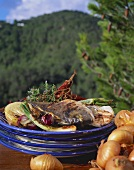 Grilled bream and vegetables against mountainous landscape