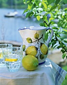 Fresh lemon, jug with lemon motif, water with lemon slices