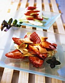 Two plates of grilled asparagus with strawberries