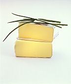 Halved pack of butter in wrapper with chives