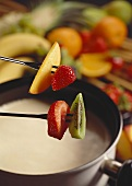 White chocolate fondue with fruit on fondue forks