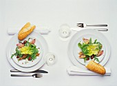 Table laid for two (with salad and baguette)