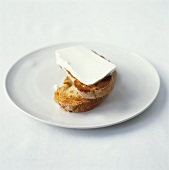 Toasted baguette slices with ricotta on white plate