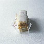 Iced, filled puff pastry slices in paper