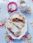 Three pieces of cherry strudel with custard