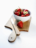 Several strawberries in a small bowl on a wooden board