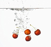 Cherries falling into water
