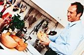Mann bereitet Hähnchen im Tontopf (Römertopf) zu