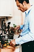 Mann legt Koriander auf Hähnchen im Tontopf (Römertopf)