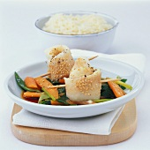 Steamed fish rolls with wasabi on a bed of vegetables