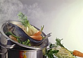 Fish and vegetables in the steamer insert of a pan