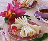 Folded napkin and pieces of cake on plate, lily
