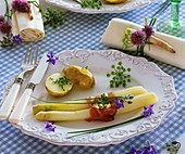 Cooked white asparagus with ham and potato