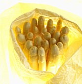 White asparagus spears wrapped in yellow paper