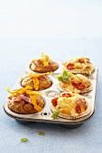Pumpkin muffins and mozzarella & tomato muffins in muffin tin