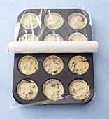 Muffin mixture in muffin tin covered with clingfilm