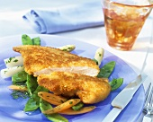 Breaded chicken escalope on vegetables