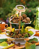 Nuts and autumn leaves on tiered stand