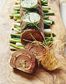 Rolled roast of beef and veal fillet on spring onions