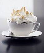 Red berry compote with meringue topping, served in a cup