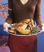 Hands holding roast turkey on a platter