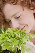 Young woman smelling basil