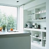 Helle Küche mit offenen Schränken, einer Espresso-Maschine und Kochinsel vor Panoramafenster