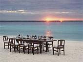 Ein gedeckter Tisch am Strand bei Sonnenuntergang