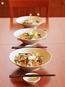 A row of bowls filled with oriental noodles and prawns