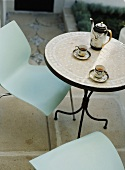 Runder Metalltisch mit Mosaikplatte und asiatischem Teeset im Garten