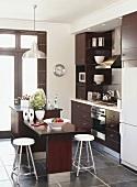 Küche mit dunkel braunen Küchenschränken und Kochinsel mit integriertem Esstisch
