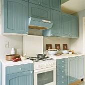 Eine Landhausküche mit blau-grauen Schrankfronten und einem Gasherd