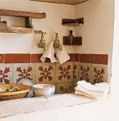 Eine rustikale Spüle mit gemusterten Wandfliesen und dreckigem Geschirr