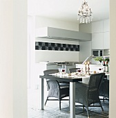 Gedeckter Tisch in einer modernen Küche mit grauen Korbstühlen und Steinfliesen