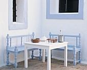 Sitzecke im Freien mit hellblauen Sitzbänken, weißem Tisch mit Tellerstapel, Tajine und Getränke