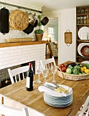 Country house kitchen with rustic dining table, stack of plates, wine glasses, red wine and basket of vegetables