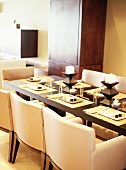 Place setting, place mats and decorations on exotic-wood table with replica designer armchairs