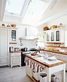 weiße, nostalgische Landhausküche mit großer Lichtquelle in der Dachschräge