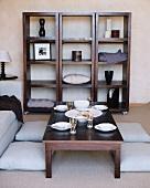 Quadratisches Holzregal auf Rollen, hinter einem für vier Personen gedeckten Wohnzimmertisch mit Bodenkissen rundherum