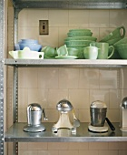 Crockery and other kitchen utensils on metal shelving against tiled wall
