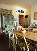 Rustic, simple dining room with plain wooden table, flea-market finds and pantry