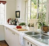 Küchenzeile mit Spüle, Holzschneidebrett und Alkoholflaschen in der Ecke